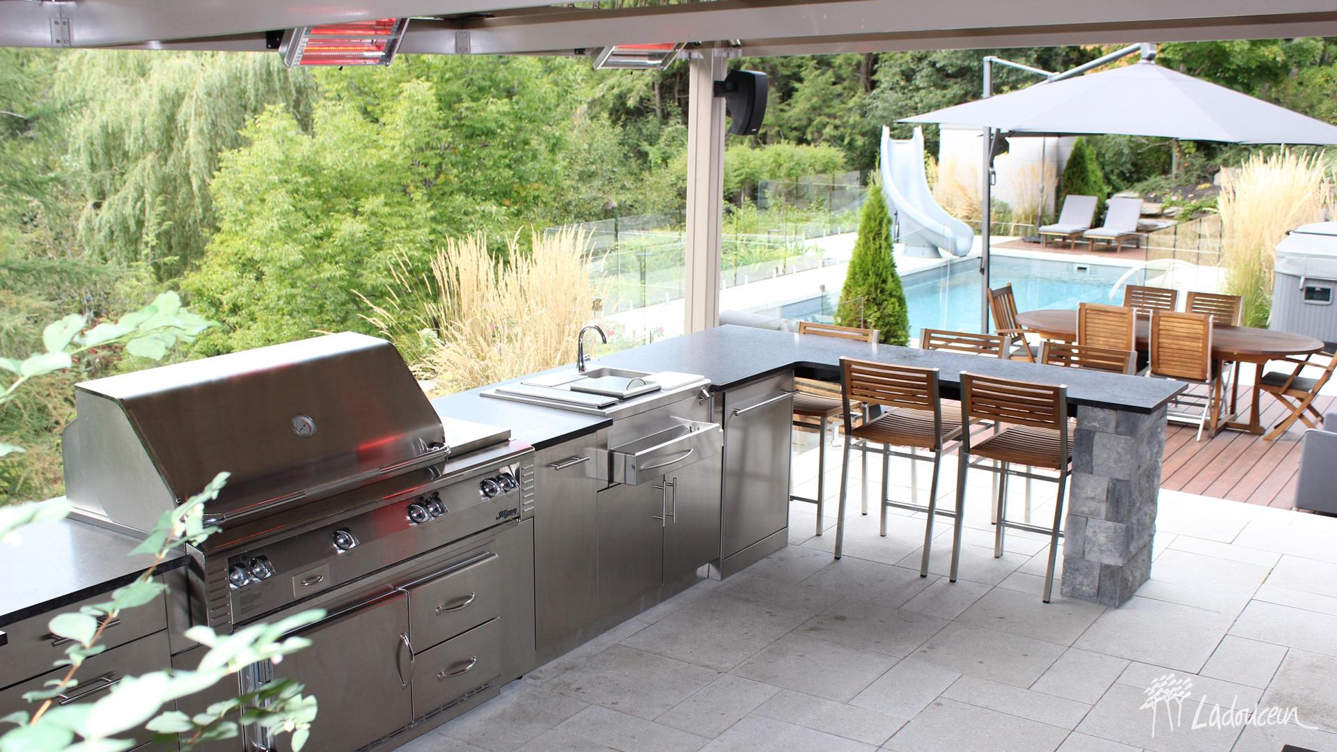 Cuisine extérieure dotée d'un comptoir en granite. Aménagement de la cour-arrière, pergola SunLouvre et chauffe-terrasse