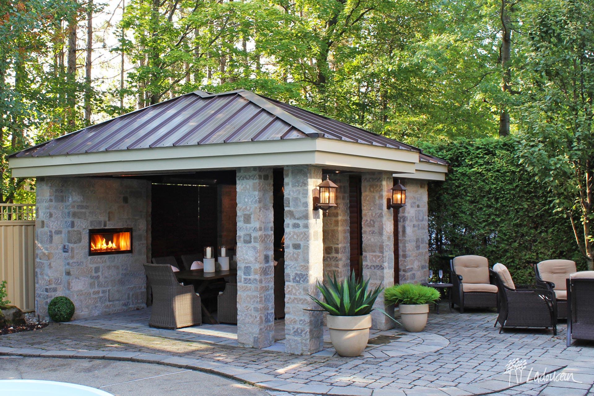 Cuisine exterieure sous un pavillon en pierre contemporaine avec foyer integree mobilier de jardin et pave uni designe par ladouceur