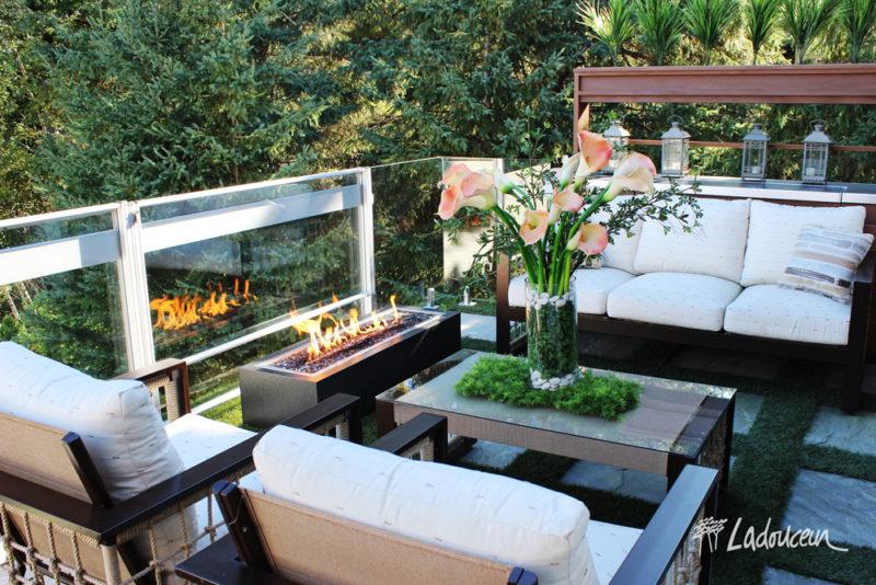 Espace lounge meublé de mobilier haut de gamme et d'un foyer à l'éthanol aménagé sur une terrasse