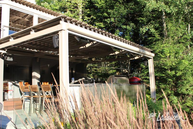 La pergola à lames orientables en aluminium protège de pluie et du soleil.