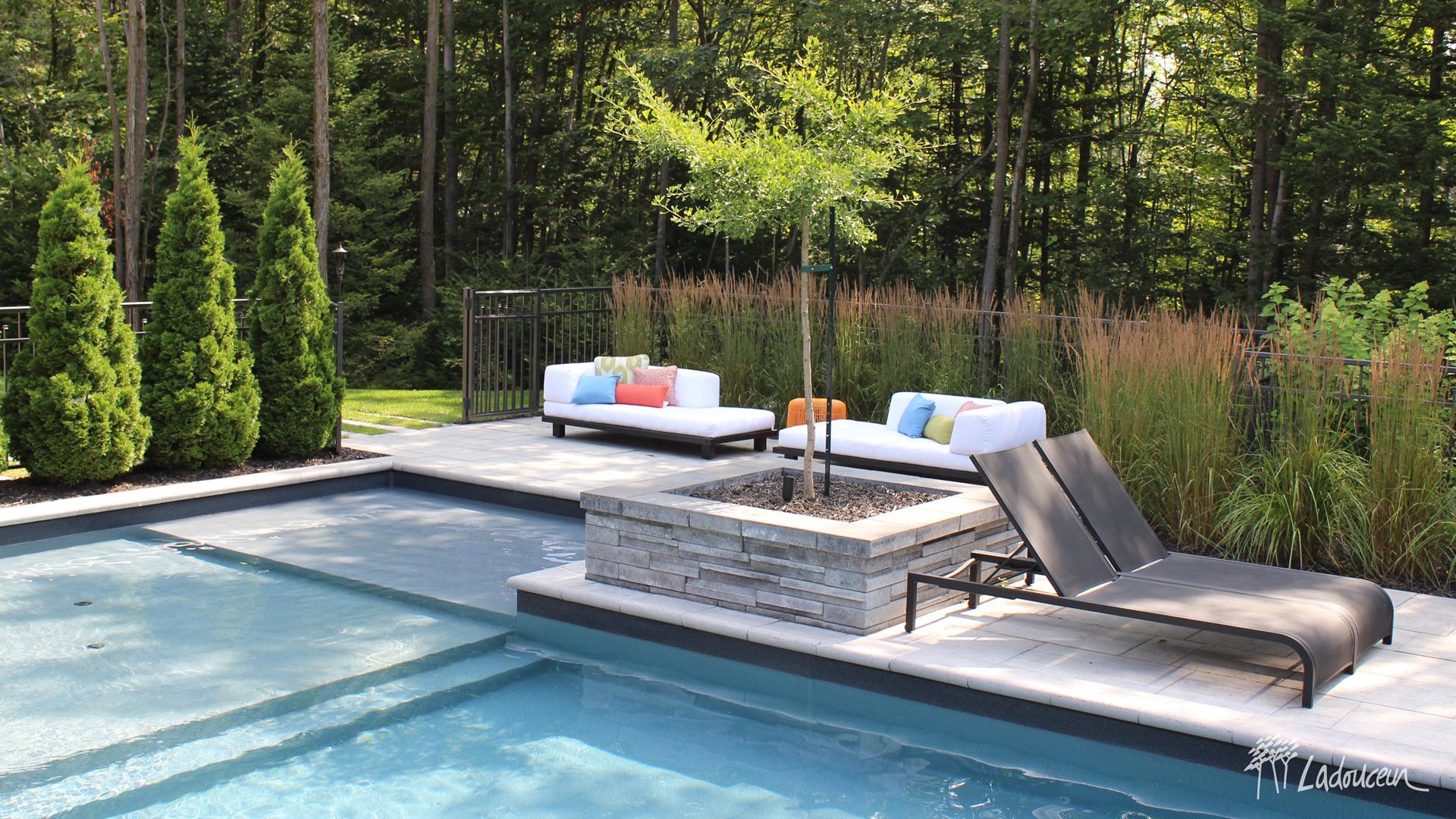 Espace détente en bordure de la piscine avec mobilier lounge et végétaux ladouceur