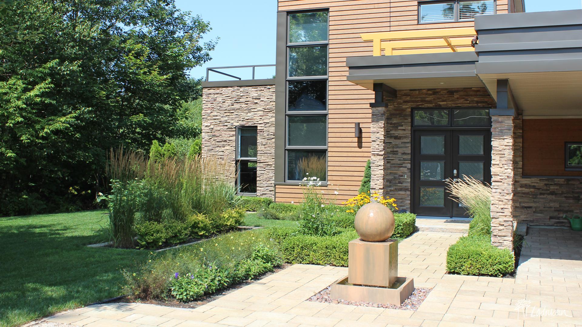 Aménagement paysager de façade contemporain fontaine d'eau oeuvre d'art et pavé et béton par Ladouceur paysagiste