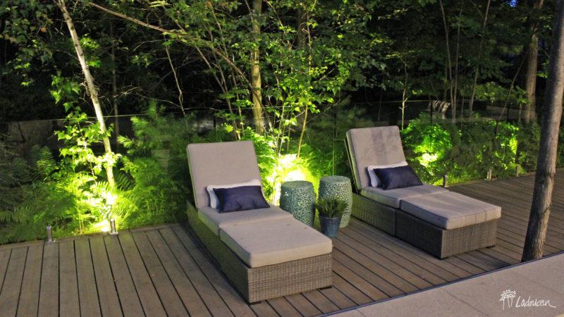 Éclairage paysager espace détente mobilier lounge chaises longues bord de piscine clôtures de verre patio en bois composite paysagiste Ladouceur